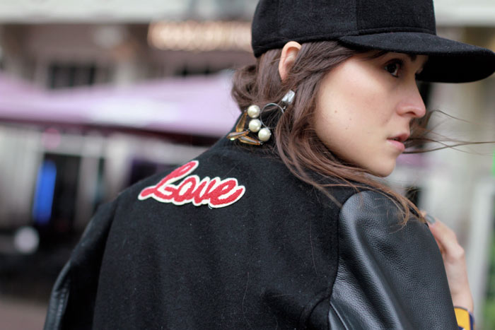 Fashion blogger Andy Torres from StyleScrapbook wearing baseball cap, statement earings and varsity jacket