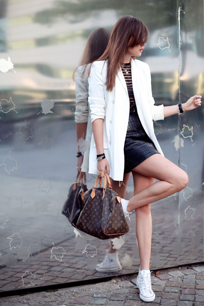 Andy Torres wearing a white blazer and a leather skirt