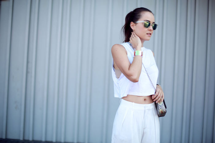 Andy Torres wearing white wide legged pants and Neri Karra bag